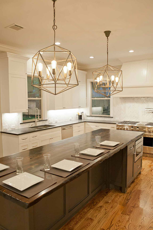 Kitchen with white cabinets, a large island with wood top and bar-style seating, and modern chandeliers.