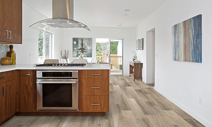 A modern open kitchen with natural wood finished cabinets and white countertops on wide strip luxury vinyl floors.